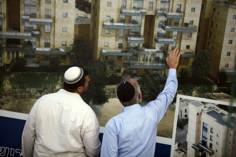 <p>Israelis stand next to sales promotion sign after a corner stone laying ceremony for a new Jewish neighborhood on August 11, 2013 in East Jerusalem, Israel. Israel's Housing Ministry announced Sunday the marketing of land for the immediate construction of nearly 1,200 new units in Jewish neighborhoods in East Jerusalem and the West Bank settlement blocs.</p>