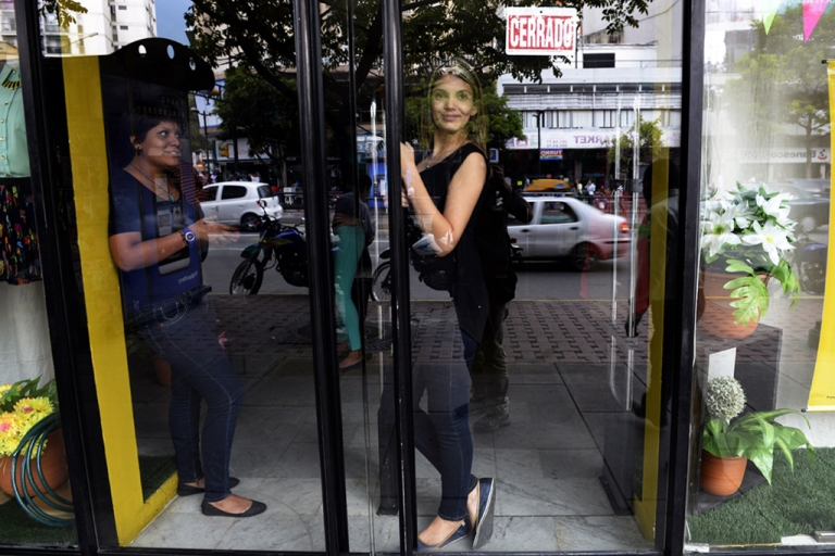 <p>Employees of a shop closed due to a blackout wait for power to be restored in Caracas, Venezuela, on Sept. 3, 2013. Widespread blackouts paralyzed Venezuela's capital and several states across the country, but there was no official explanation for the cause.</p>