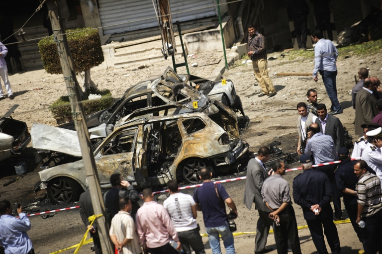 <p>Egyptians gather at the site of a bomb that targeted the convoy of the Egyptian Interior Minister Mohammed Ibrahim in Cairo on September 5, 2013. It was the first such attack in Cairo in years.</p>