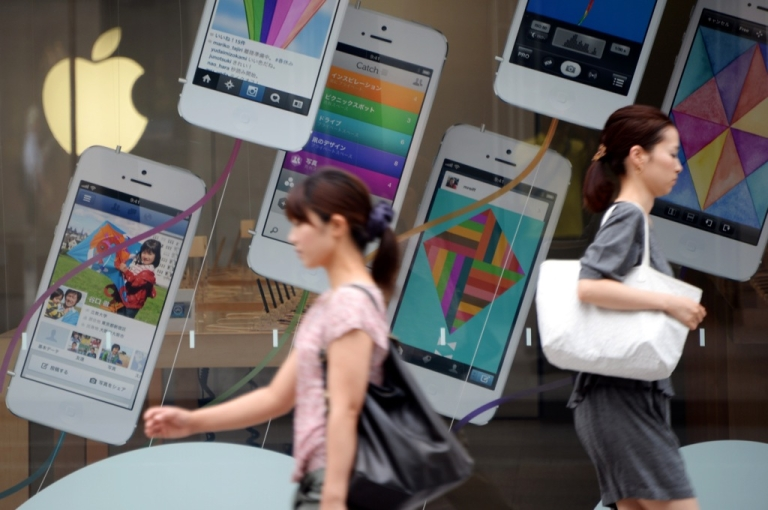 <p>Pedestrians walk past advertisements for the iPhone 5 at the Apple store in central Tokyo on September 6, 2013.</p>