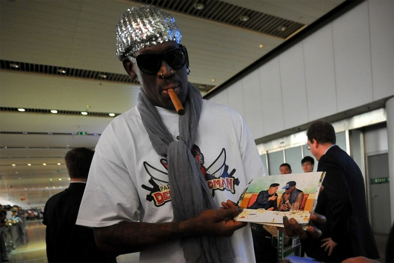 <p>Family album: former NBA star Dennis Rodman shows pictures of himself with Kim Jong Un on the way home from a trip to North Korea, at Beijing airport on Sept. 7, 2013. Rodman says the supreme leader, who reportedly has a baby daughter, is a