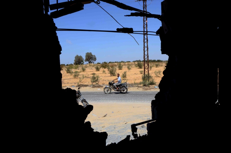 <p>A man is seen riding his motorbike through a wall that was destroyed by an attack by Egyptian Army the day before in a village on the outskirt of the Northern Sinai town of Sheik Zuweid on September 10, 2013. A series of attacks in Egypt's restive Sinai Peninsula, mostly against soldiers, killed at least four people, security officials said. The violence comes as the Egyptian military presses its campaign in Sinai to quell an insurgency that surged after the army overthrew Islamist president Mohamed Morsi on July 3.</p>