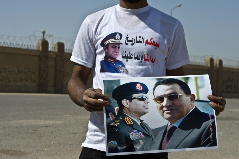 <p>A supporter holds a poster featuring Egyptian toppled president Hosni Mubarak (R) and General Abdel Fattah al-Sisi (L) on September 14, 2013 in Cairo outside the Police Academy, where Mubarak appeared in court for the second time since his release from Cairo's Tora prison. Mubarak faces an array of charges, including complicity in the deaths of some 850 people killed in the Arab Spring-inspired uprising against him, and corruption.</p>