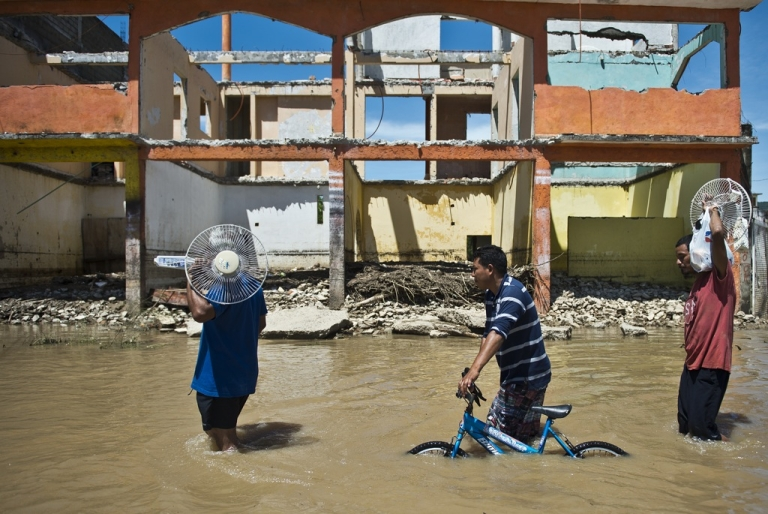 <p>Local residents wade through a flooded street in Acapulco, state of Guerrero, Mexico, on September 18, 2013 as heavy rains hit the country. Two tropical storms, Ingrid and Manuel, hit large swaths of the country during a three-day holiday weekend, triggering landslides and causing rivers to overflow in several states.</p>