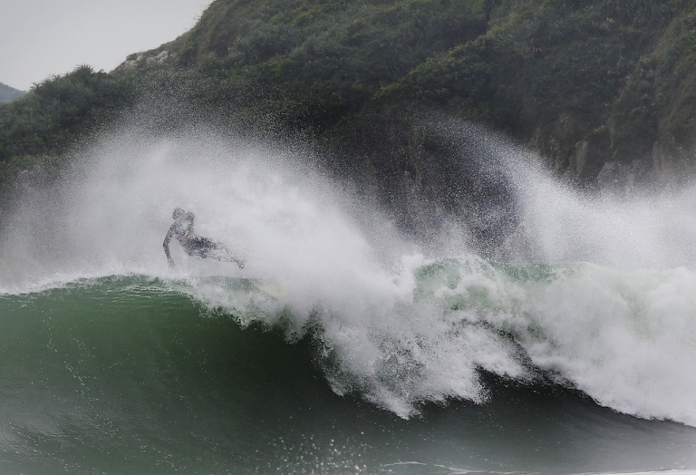 <p>A surfer jumps from his surfboard while catching an unusually large wave at Big Wave Bay on September 22, 2013 in Hong Kong. Typhoon Usagi missed the island on Sunday but caused heavy winds and rains.</p>