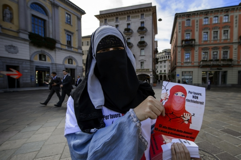 <p>Islamic Central Council of Switzerland (ICCS - CCIS) member Nora Illi, one of the few Swiss women wearing the niqab, distributes flyers against a cantonal vote on banning face-covering headgear in public places, on September 18, 2013 in Lugano.</p>