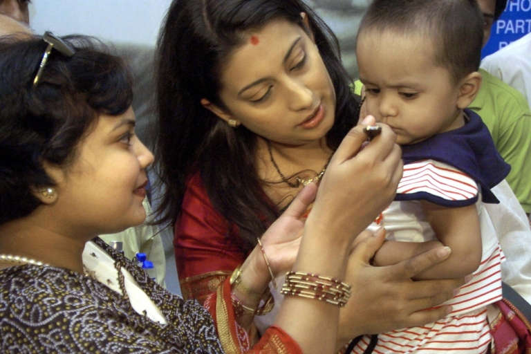 <p>World Health Organisation (WHO) and Oral Rehydration Salts (ORS) Goodwill Ambassador Smriti Irani (C) holds a child being fed an ORS solution.</p>