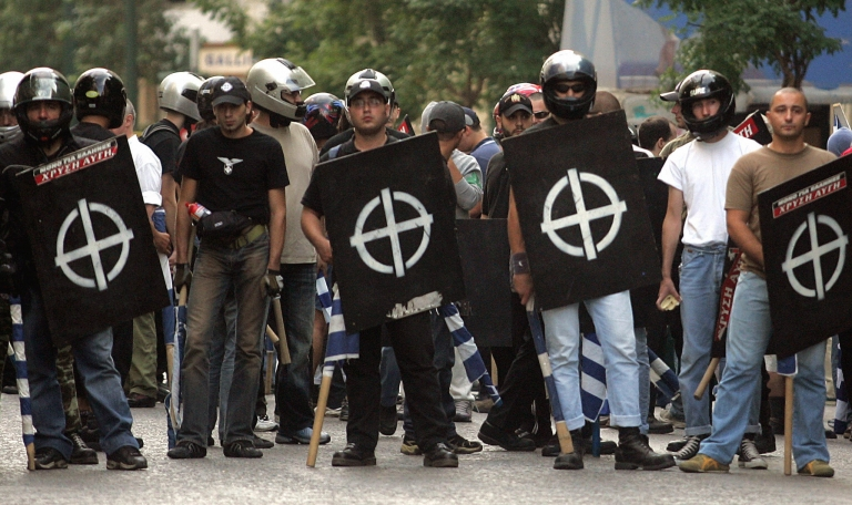 <p>Extreme right-wing group Chryssi Avgi (Golden Dawn) members hold greek flags and their's faction's emblem 17 september 2005 during a demonstration outside their headquarters in central Athens to protest a ban on a planned gathering of European neo-Nazi and fascist parties in Greece.</p>