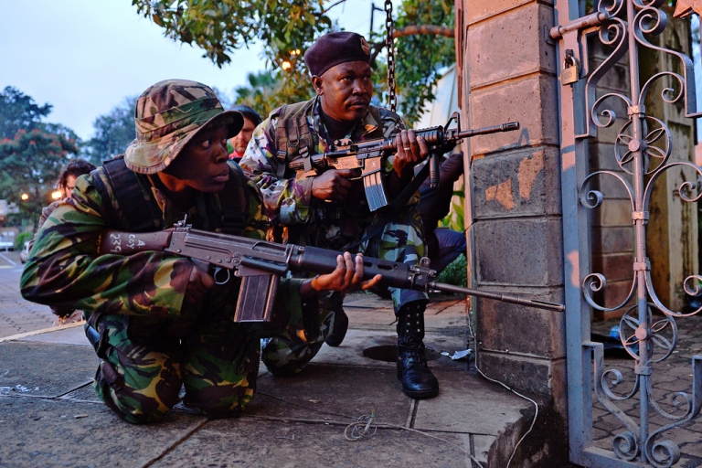 <p>Kenyan soldiers take cover after heavy gunfire near Westgate mall in Nairobi on September 23, 2013. Kenyan Defense troops remain inside the mall, in a standoff with Somali militants after they laid siege to the shopping centre shooting.</p>