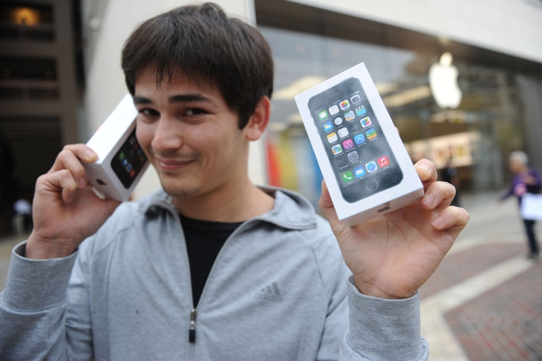 <p>Kerim Muhammet poses with his two new Apple iPhone 5S models after waiting in line overnight in Glendale, California, on September 20, 2013. Apple launched two new models of the iPhone today, the iPhone 5S, which is an updated version of the iPhone 5, and a less expensive iPhone 5C.</p>