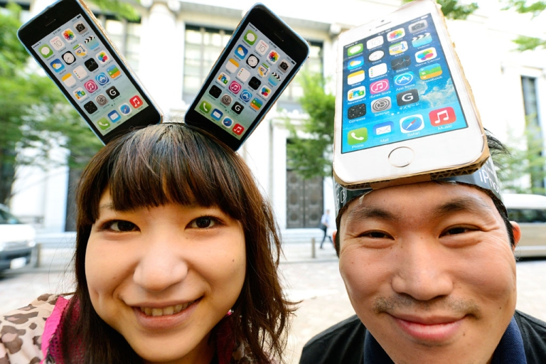 <p>Apple fans wearing handmade iPhone headpieces smile as they wait to purchase the new iPhone 5s outside an outlet of Japan's biggest mobile carrier, NTT Docomo, in Tokyo on September 20, 2013.</p>