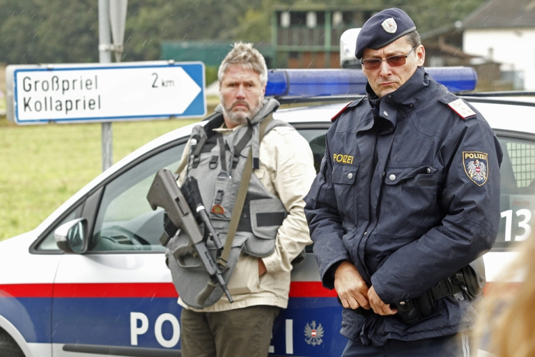 <p>Policemen block a road on September 17, 2013 near Grosspriel, some 65 kilometers west of Vienna, where a man entrenched himself with a hostage in a farmhouse.</p>