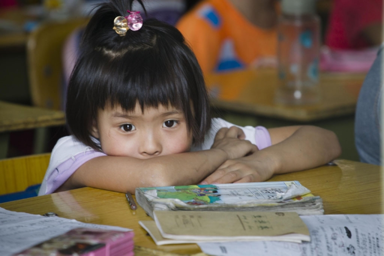 <p>A young girl studies at an illegal migrant school ordered to close in Beijing, China. In a country facing geographical and economic challenges to its education system, an estimated 400 million people can't speak Mandarin, the national language, state media reported on Sept. 5, 2013.</p>