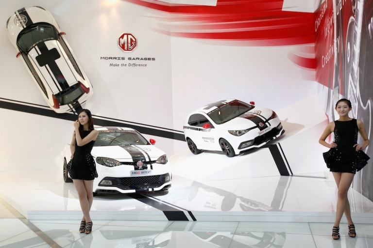 <p>Models stands beside a MG6 Btcc car during the 2012 Beijing International Automotive Exhibition. China's capitalism may be cut-throat like America's, but it's played under an entirely different set of rules, says Andrew Hubert, publisher of ChinaSolved.com.</p>
