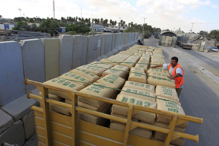 <p>A Palestinian worker checks a truck loaded with bags of cement after it crossed into Rafah town through the Kerem Shalom crossing between Israel and the southern Gaza Strip on Sept. 22, 2013. Israel permitted delivery of cement and steel for use by the private sector into the Gaza Strip for the first time since 2007.</p>