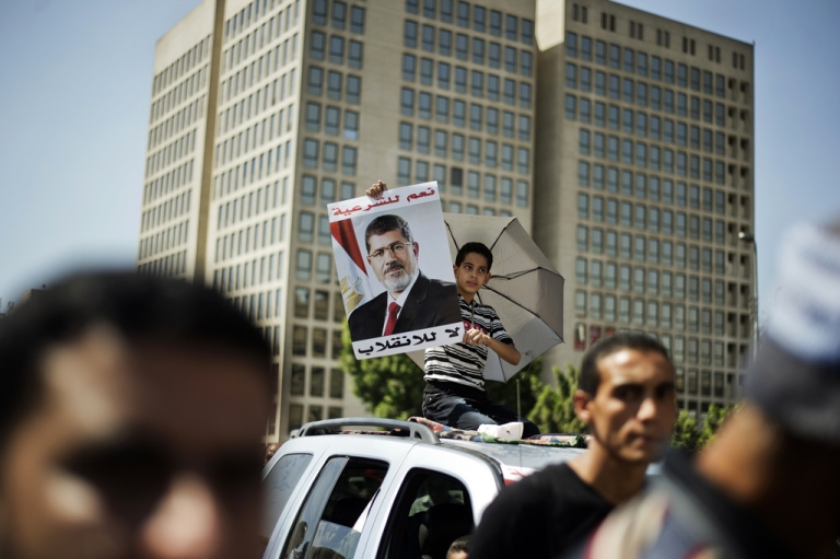<p>An Egyptian child carries a portrait of ousted president Mohamed Morsi during a demonstration in support of Morsi in Cairo, on August 9, 2013.</p>