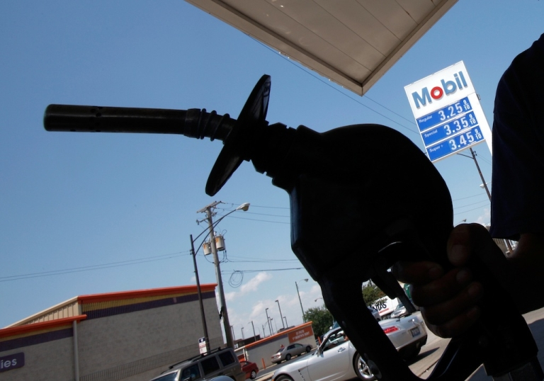 <p>A car owner fills up at an Exxon Mobil gas station in Chicago on July 29, 2010.</p>