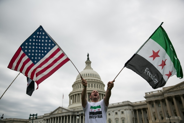 <p>WASHINGTON, DC - SEPTEMBER 9: Jehad Sibai waves flags during a rally in support of possible U.S. military action in Syria, on Capitol Hill, on September 9, 2013 in Washington, DC. A Syrian minister has called the US-Russia chemical weapons deal struck in Geneva on Saturday a