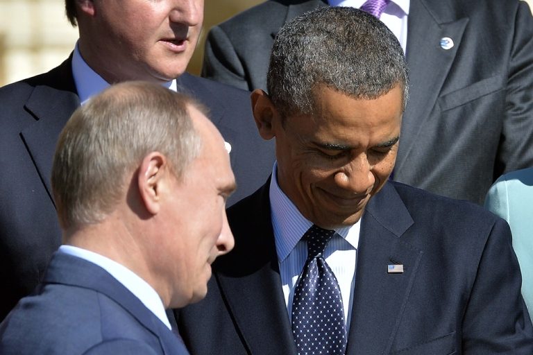 <p>Russian President Vladimir Putin (L) walks past US President Barack Obama as he arrives to pose for the family photo during the G20 summit on September 6, 2013 in Saint Petersburg. On Saturday, the United States and Russia came to an agreement on Syria's chemical weapons stockpile during intense negotiations in Geneva.</p>