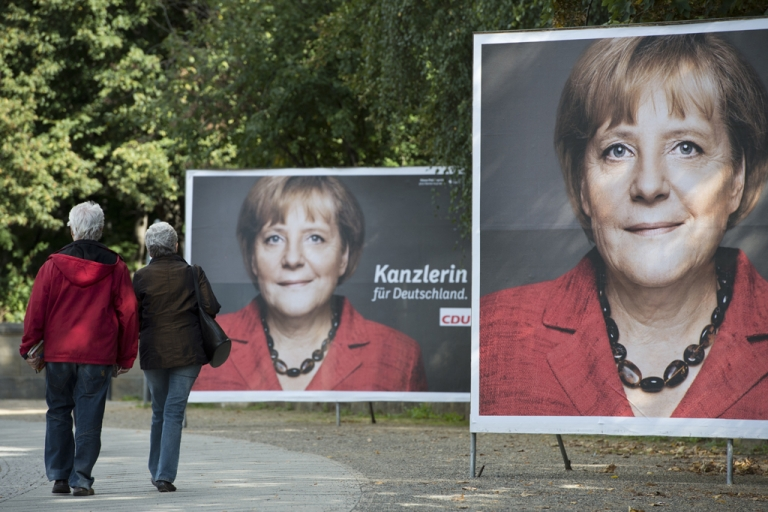 <p>A couple makes their way past election posters featuring German Chancellor Angela Merkel in Berlin September 17, 2013.  Germany goes to the polls in general elections on September 22, 2013.</p>