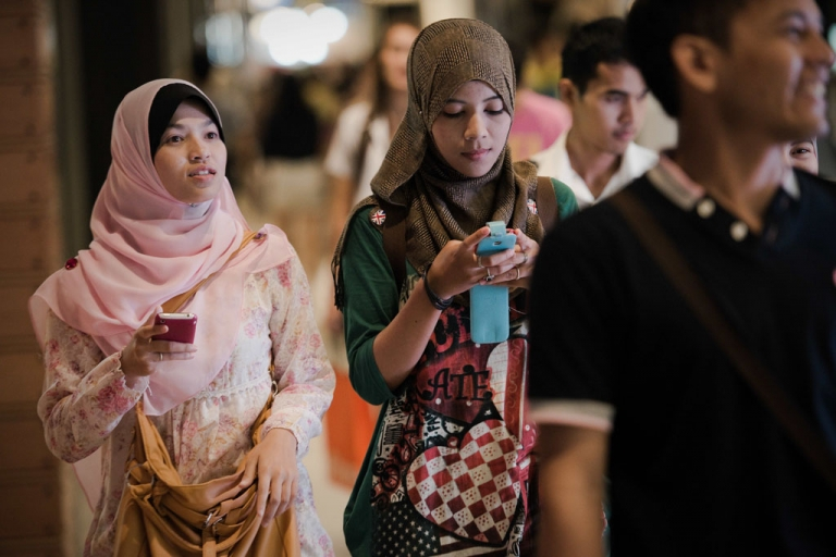<p>Two friends check their smartphones as they walk in a shopping mall in Bangkok on March 21, 2013. Global smartphone sales are expected to reach 1 billion in 2013 alone thanks to cheaper devices and inroads into emerging markets.</p>