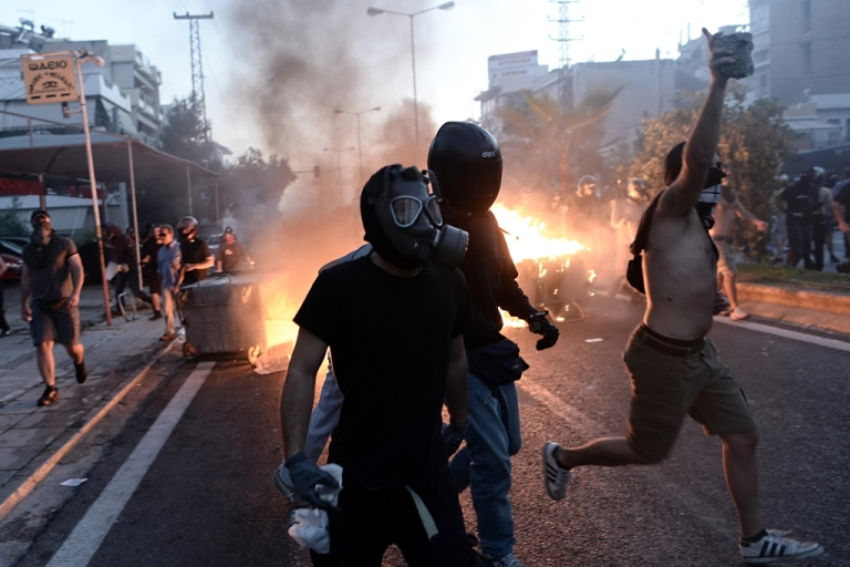 <p>Anti-fascist demonstrators clash with riot police in Athens on September 18, 2013, after a leftist musician was murdered by a suspected neo-Nazi. Pavlos Fyssas, a 34-year-old left-wing hip hop singer, was stabbed to death early today morning outside a Keratsini cafeteria.</p>