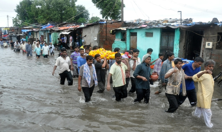 <p>Indian mourners carry a body during a funeral procession as they wade through a flooded street in Vadodara, some 110 kms from Ahmedabad on September 24, 2013 .</p>