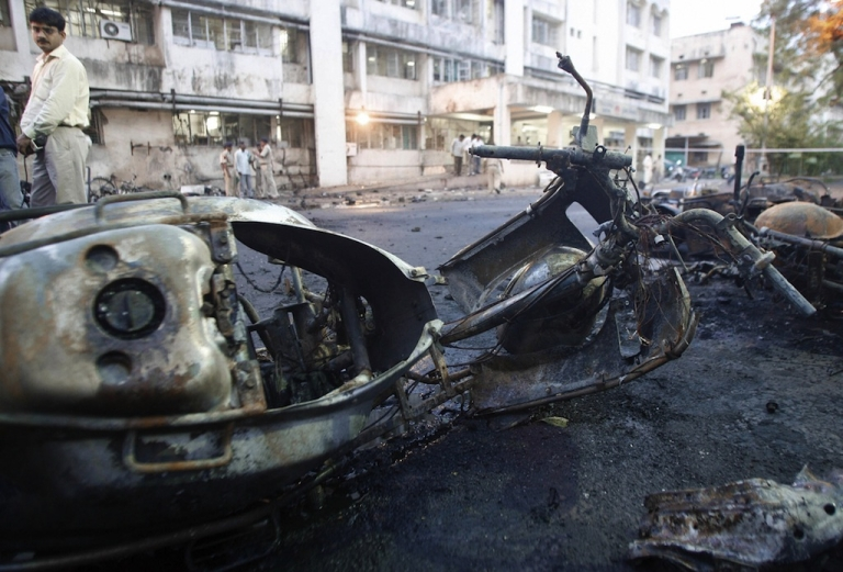 <p>A journalist looks at the remains of motorcycles at a bomb blast site outside a hospital in Ahmedabad on July 27, 2008.</p>