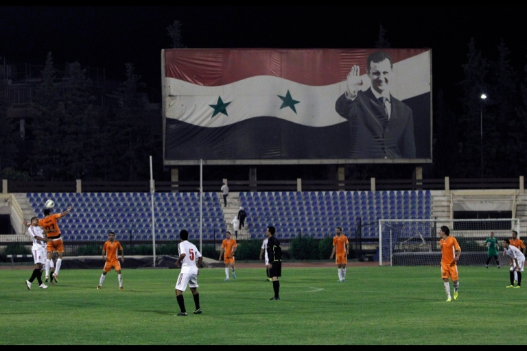 <p>Syrian football players compete in front of a giant banner featuring Syrian President Bashar al-Assad during the Syrian Cup football match between Al-Wahda and the army's Al-Jaish teams on Sept. 10, 2013 in Damascus. Meanwhile, on the international diplomatic field, fumbles abound as the Russians intercept Kerry's desperation pass on the Syrian conflict.</p>