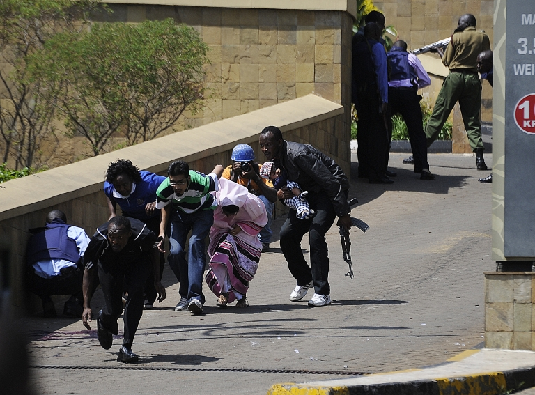 <p>A policeman carry's a baby to safety after masked gunmen stormed an upmarket mall and sprayed gunfire on shoppers and staff, killing at least six on September 21, 2013 in Nairobi. The Gunmen have taken at least seven hostages, police and security guards told an AFP reporter at the scene.</p>