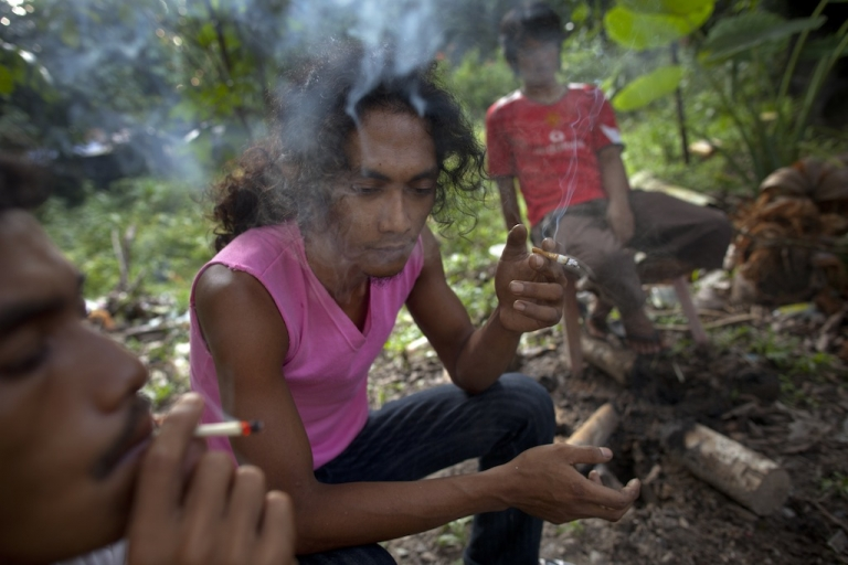 <p>A Thai man stirs cough syrup into the cheap, popular narcotic drink called 4x100 in Narwathiwat, Thailand, in 2011. The drink also contains Kratom, a stimulant leaf that Thailand's justice minister wants to legalize as an alternative to meth-amphetamine.</p>