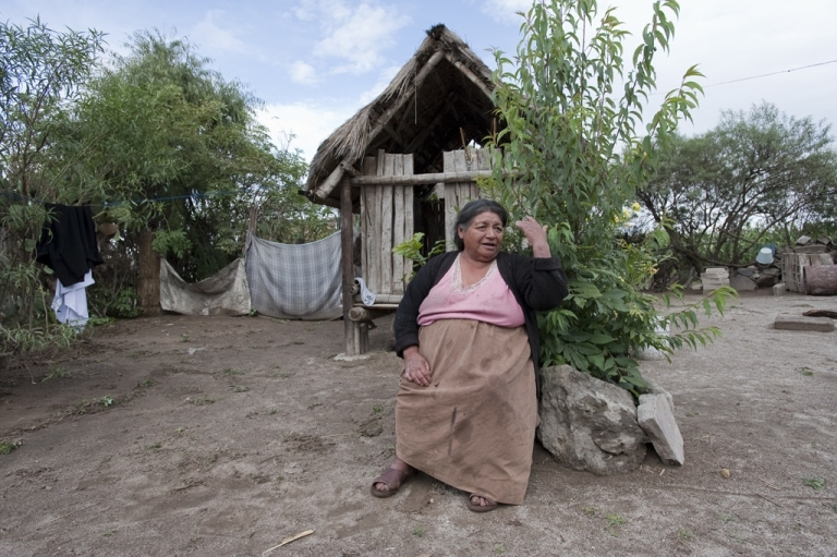 <p>Maria Rufina Suarez sits outside her home in Vicente Guerrero, Mexico, listening to the benefits of registering with the government's