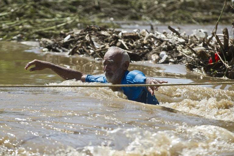<p>A man wades through a flooded street in Acapulco, Mexico.</p>