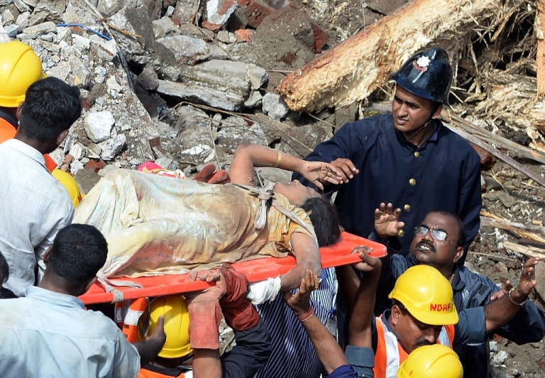 <p>Firefighters bring out a female survivor from the rubble at the site of a building collapse in Mumbai on September 27, 2013. A five-storey residential block collapsed in Mumbai at daybreak killing at least three people and leaving up to 70 feared trapped inside, in the latest building disaster to hit India's financial capital.</p>