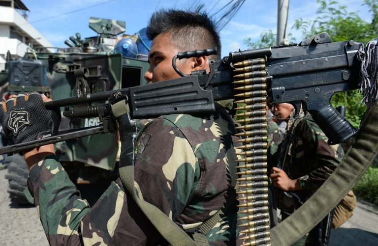 <p>A soldier prepares to board an armored personnel carrier headed for the outskirts of Zamboanga city in Mindanao, Philippines, in pursuit of Muslim rebels, on September 17, 2013.</p>
