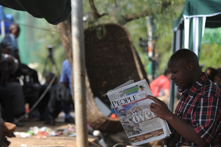 <p>A man reads today's paper in Nairobi on September 25, 2013 after Kenyan forces took back control of  Westgate mall following a deadly four-day siege that left more than 60 people dead.</p>