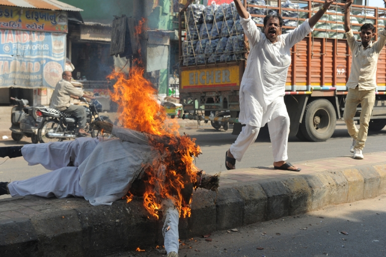 <p>Gujarat Congress party supporters shout slogans as they burn a fireworks-stuffed effigy of Gujarat state Chief Minister Narendra Modi during a strike in Ahmedabad on September 6, 2013.</p>