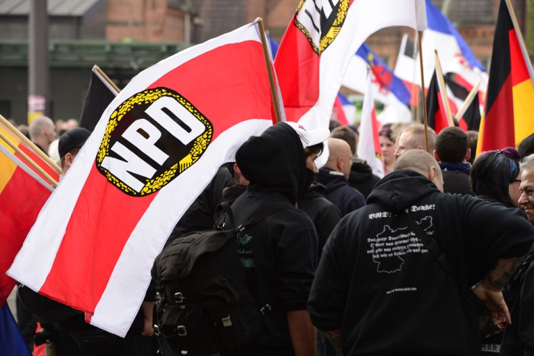 <p>Supporters of Germany's far-right National Democratic Party (NPD) wave flags as they take part in a demonstration on May 1, 2013 in Berlin.</p>