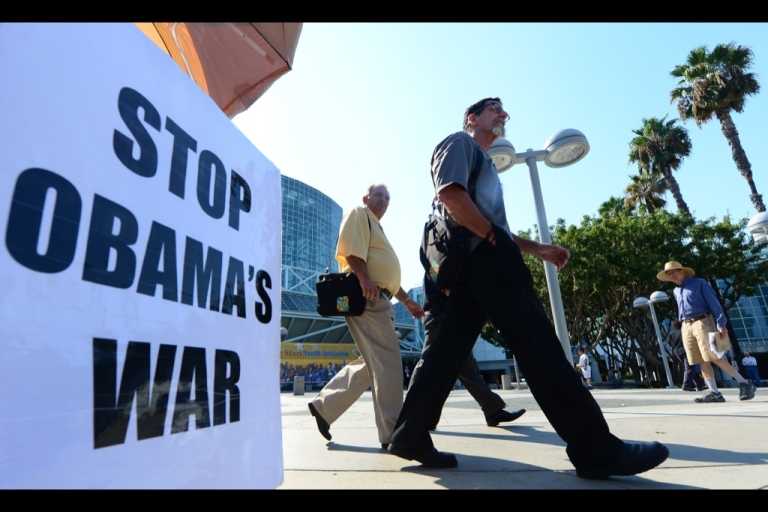 <p>Pedestrians walk past a placard that reads 'Stop Obama's War' outside the Los Angeles Convention Center on Sept. 9, 2013, as US President Barack Obama said a Russian plan to secure Syria's chemical weapons could be a 'significant breakthrough' but warned he had not taken US strikes off the table.</p>