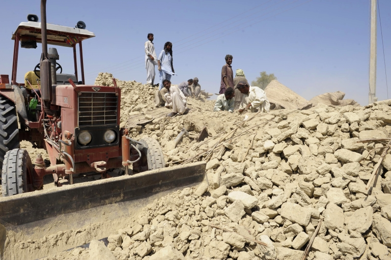 <p>Pakistani earthquake survivors search through the debris of their collapsed houses in the devastated district of Awaran on Sept. 25, 2013.</p>