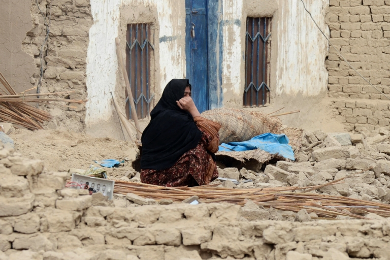 <p>A Pakistani earthquake survivor sits near her collapsed mud house in the southwestern Baluchistan province on April 17, 2013. Another earthquake struck the same region on September 24, 2013.</p>