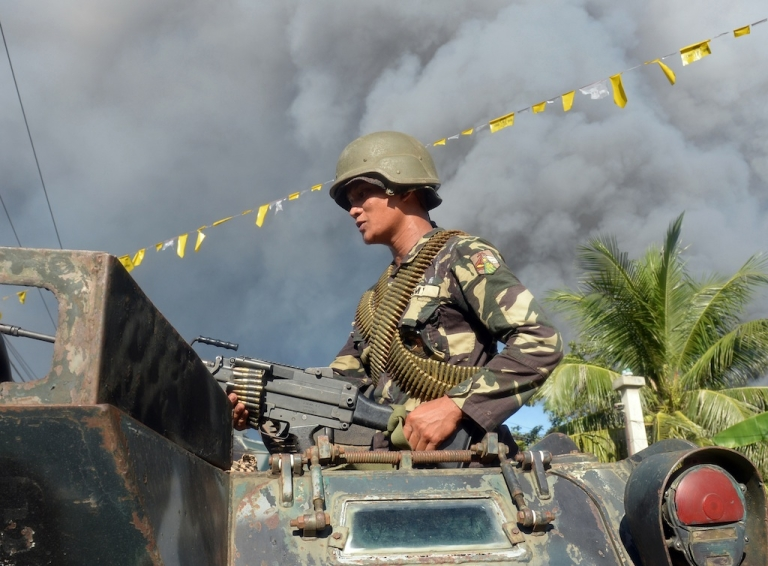 <p>A Philippine soldier standing in an armoured personnel carrier adjusts his machine gun prior to an assault on Muslim rebel positions as the stand-off in the southern city of Zamboanga enters its fifth day on Sept. 13, 2013.</p>