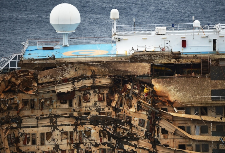 <p>Italy's Costa Concordia cruise ship begins to emerge from water near the harbour of Giglio Porto on Sept. 17, 2013.</p>