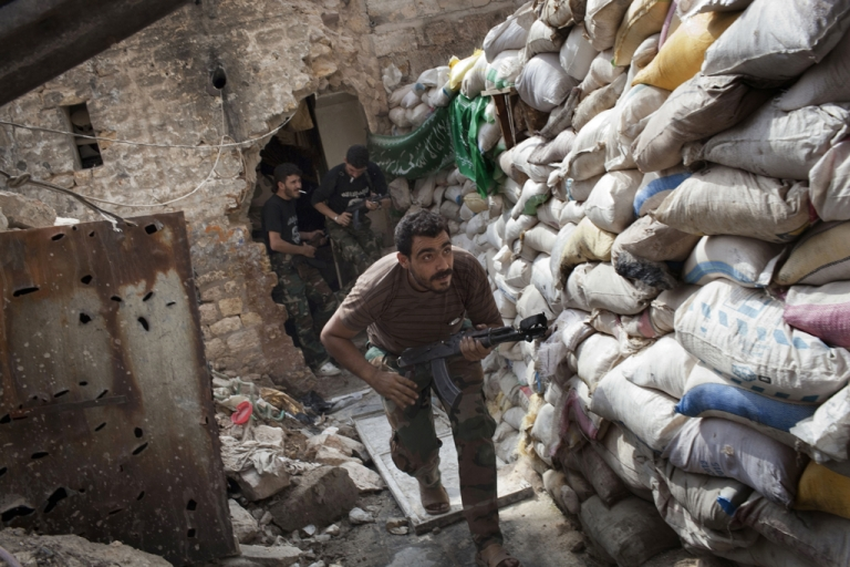 <p>Rebel fighters duck as they run behind a barricade to avoid being fired at by Syrian regime forces in the Old City's front line in Aleppo on September 18, 2013.</p>