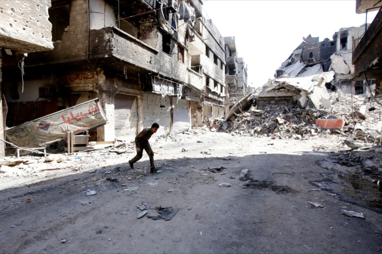 <p>A fighter of the Popular Front for the Liberation of Palestine General Command (PFLP-GC) runs across a street in the Yarmouk refugee camp in the Syrian capital Damascus on Sept. 12, 2013, following fighting against rebel forces who control 75 percent of the camp. The PFLP-GC has been allied with Syrian President Bashar al-Assad's government.</p>