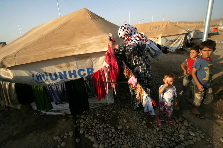 <p>A Syrian-Kurdish refugee woman hamgs out her laundry on a clothesline outside a tent provided by the UNHCR at the Quru Gusik refugee camp in the Kurdish region of northern Iraq.</p>