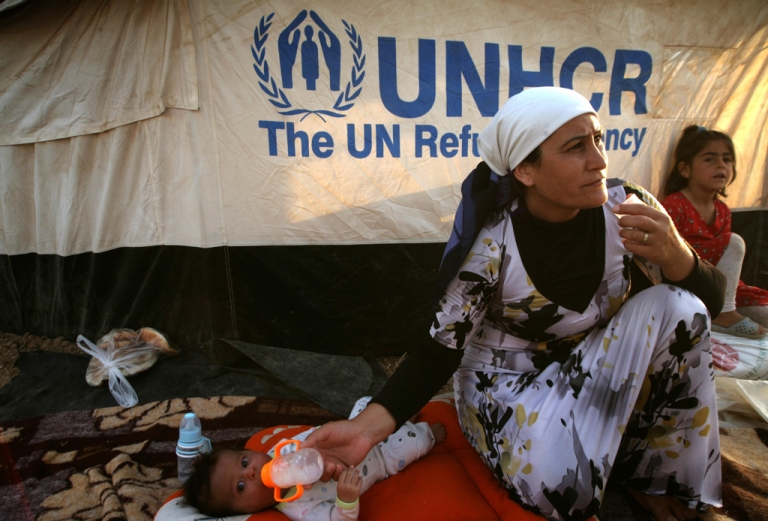 <p>A Syrian-Kurdish refugee feeds her child outside a tent provided by the UNHCR at the Quru Gusik refugee camp in the Kurdish region of northern Iraq, on August 27, 2013.</p>