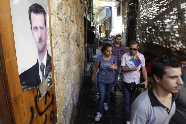 <p>People walk in a narrow alley past a poster featuring Syrian President Bashar al-Assad in the capital Damascus on September 16, 2013.</p>