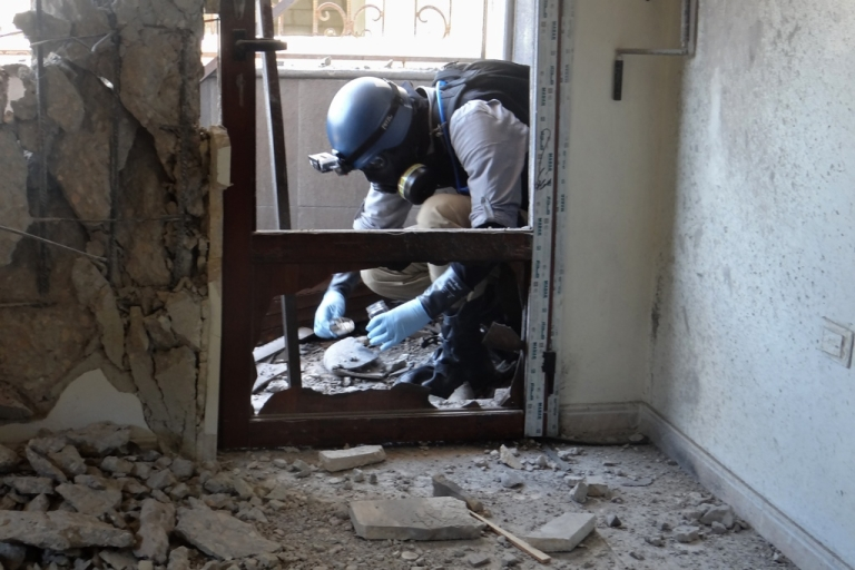 <p>A UN arms expert collects samples in a Damascus suburb Aug. 29 during an investigation into chemical weapons attacks.</p>