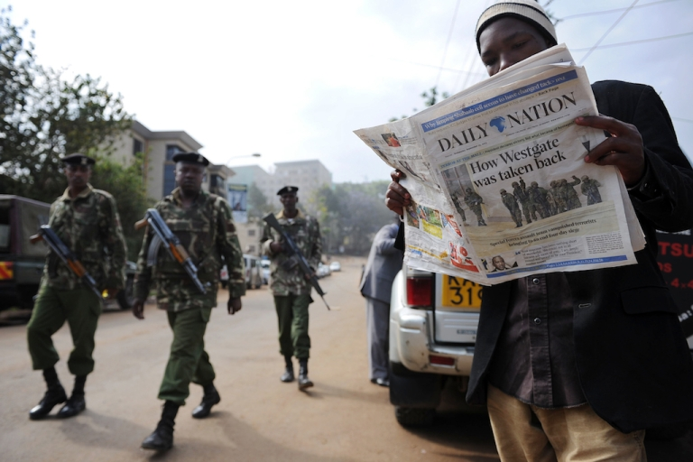 <p>A man reads today's paper in Nairobi on Sept. 25, 2013 after Kenyan forces took back control of Westgate mall following a deadly four-day siege that left more than 60 people dead.</p>